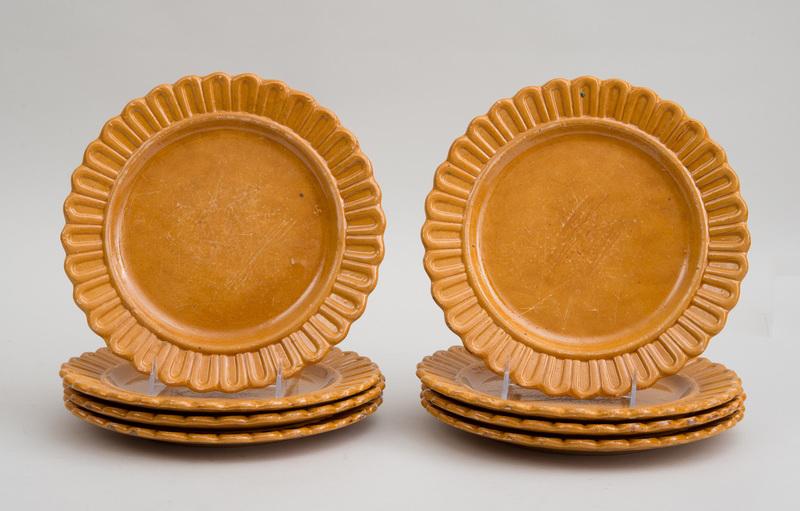 SET OF EIGHT PUMPKIN-GLAZED POTTERY PLATES
