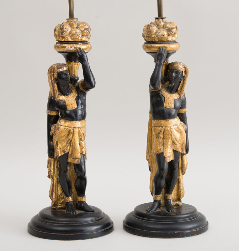 PAIR OF CONTINENTAL CARVED, BLACK-PAINTED AND PARCEL-GILT FIGURES OF ANCIENT EGYPTIAN SERVANTS, MOUNTED AS LAMPS