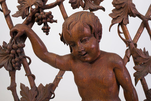 CONTINENTAL CARVED AND PIERCED OAK WALL PANEL OF A CHILD PRESSING GRAPES