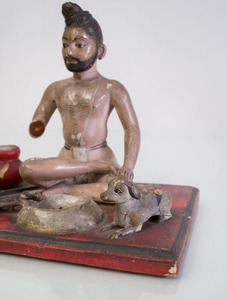 EIGHT INDIAN CARVED AND PAINTED WOOD FIGURES IN PRAYER