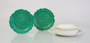 EIGHT GREEN MAJOLICA BRAMELD GREEN GLAZED POTTERY TIERED-LEAF PLATES AND A CREAMWARE BASKET WITH UNDERPLATE