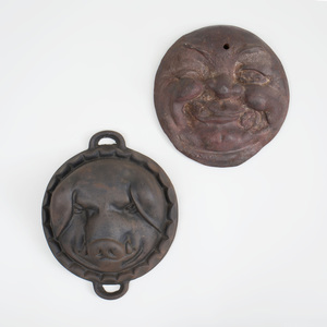 Cast Iron Smiling Moon Face and a Cast Iron Two-Handled Pig Face Mold