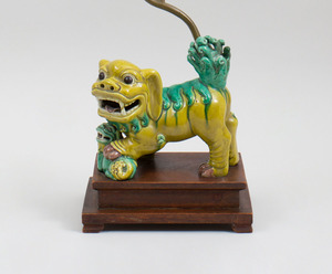 CHINESE YELLOW AND GREEN GLAZED MODEL OF A BUDDHISTIC LION MOUNTED AS A LAMP