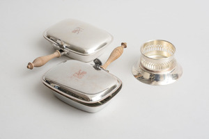 PAIR OF AMERICAN CRESTED SILVER-PLATED SILENT BUTLERS AND A KENNETH TURNER, LTD. SILVER-PLATED BOTTLE COASTER