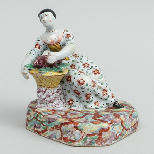 Dutch Polychrome Delft Figure of a Seated Woman with Basket of Grapes
